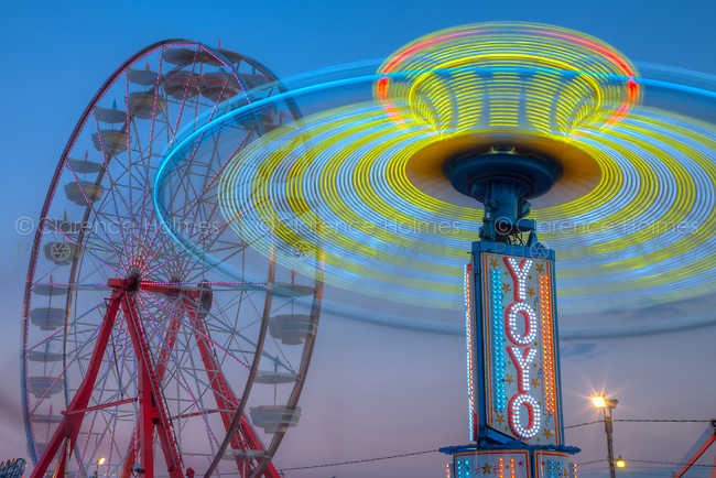 AUGUSTA, NJ - AUGUST 13: The colorfully illuminated Gentle Giant Ferris Wheel and Yo Yo spin against the sky at dusk during the New Jersey State Fair on August 13, 2010 at the Sussex County Fairgrounds, Augusta, New Jersey