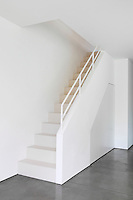 A minimalist staircase with a built in cupboard underneath.