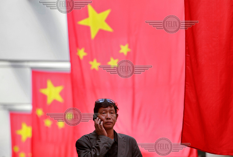 A man uses a mobile phone while standing under a row of Chinese national flags.