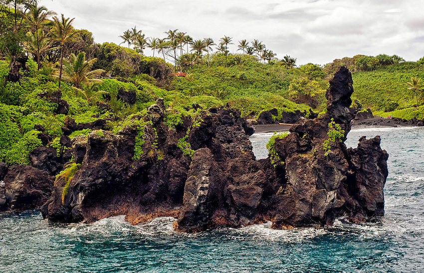 Lava rocks protrude from the ocean at Wai'anapanapa State Park, near Hana, Maui, Hawaii