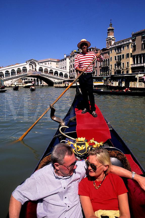 Tourists on romantic gondola ride near the famous Rialto Bridge with gondolier in picturesque Venice Ital