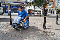 Wheelchair user finding it extremely difficult over the uneven cobblestones. This image may only be used to portray the subject in a positive manner..©shoutpictures.com..john@shoutpictures.com