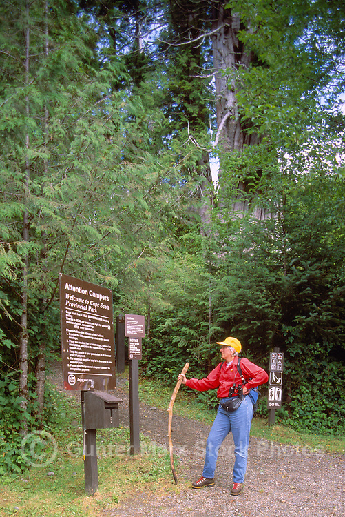Cape Scott Provincial Park, Northern Vancouver Island, BC, British Columbia, Canada - Hiker reading Sign at Start of Hiking Trail (Model Released)