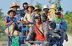 Agricultural workers ride to work in the village of Dong in northern Cambodia.