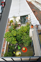 Cedarwood garden extensions have greatly increased the space of this house and on the childrens' floor the terrace is planted with lush bamboos and laurel