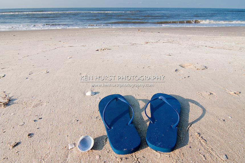 Pair of blue sandals on the sand at Holly Beach near Cameron, Louisiana on the Gulf Of Mexico.