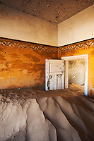 Accumulated desert sand blocks a door inside a house in Kolmanskop