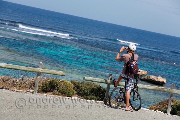A cyclist photographs the coastline at Jeannies Lookout on Rottnest Island, Western Australia, AUSTRALIA.  Exploring Rottnest Island by bicycle.  Rottnest Island, Western Australia, AUSTRALIA.