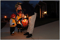 Two young boys dressed as firefighters head out for an evening of trick-or-treating. Model released