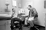 Male doctor listening to seated elderly male patient in examination room