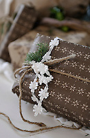 A present decorated with lace, ribbons and spruce waits to be unwrapped under the Christmas tree