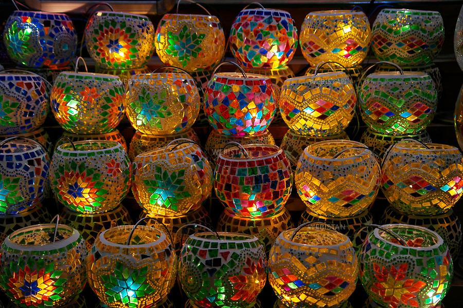 Turkey, Istanbul, Fatih District, Eminonu, Spice Bazaar, October 6, 2012Colorful glass, mosaic lanterns are sold at a stand in the Spice Bazaar. The Spice Bazaar was built in 1664 as an extension of the Yeni Camii (New Mosque). The market is called the Egyptian Bazaar in Turkish because it was built with money paid as duty on Egyptian imports. The Bazaar is stocked with exotic spices, herbs, dried fruits, Turkish delight, cheeses, nuts and jams, but also features jewelry and more recently clothes, household goods, caviar, and more high-end items. <br /> Turquie, Istanbul, District de Fatih, Eminonu, Bazar aux Epices, 6 octobre 2012Verre colore et lanternes de mosaique sont vendus sur un stand dans le bazar aux epices,  construit en 1664 comme extension de la Yeni Camii (Nouvelle Mosquee). Il est appele marche egyptien en turc, car il a ete construit avec l'argent verse a titre de droits sur les importations egyptiennes. Il est approvisionne avec des epices exotiques, herbes, fruits secs, loukoums, des fromages, des noix et des confitures, mais propose aussi des bijoux et plus recemment des vetements, des articles menagers, du caviar, et des articles haut de gamme.