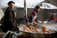 People walk past boiling eggs for sale in an alleyway in the Uighur section of Urumqi, Xinjiang, China. The city is divided between Han and Uighur ethnic groups and in 2009 saw violent clashes between the groups.