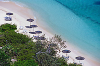 Sun umbrellas dotted along the white sand beach on Amedee Island, New Caledonia.