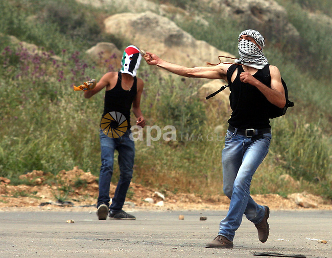 """Palestinian protesters throw stones at Israeli troops during a demonstration outside Ofer military prison near the West Bank city of Ramallah on May 1, 2012 in a show of support for prisoners held in Israeli jails. Clashes erupted between stone-throwing youths and the Israeli army, who fired tear gas, rubber bullets and a foul-smelling liquid known as """"skunk"""" to break up the demonstration. Photo by Issam Rimawi"""