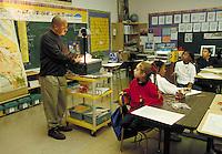 TEACHER USING AN OVERHEAD PROJECTOR IN SCHOOL CLASSROOM. ELEMENTARY STUDENTS. OAKLAND CALIFORNIA USA CARL MUNCK ELEMENTARY SCHOOL.