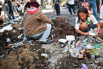 Apr. 30 - BANGKOK, THAILAND: Red Shirts clean up some of the diesel fuel soaked dirt they left to stop government troops in the Sala Daeng intersection in Bangkok. The Red Shirts moved one of their barricades in the Sala Daeng Intersection in Bangkok Friday In one of the first positive moves to take place since the Red Shirts occupied central Bangkok in early April. The barricade was moved far enough back to open one lane of traffic on  Ratchadamri Street to allow ambulance access to King Chulalongkorn Memorial Hospital, a large hospital at the intersection. Many of the patients in the hospital have been moved to other hospitals because a group of Red Shirts entered the hospital Thursday looking for Thai security personnel, who were not in the hospital. The stand off between the Red Shirts and the government enters its third month in May. The Red Shirts continue to call for Thai Prime Minister Abhisit Vejjajiva to step down and dissolve parliament and demand the return of ousted Prime Minister Thaksin Shinawatra.   PHOTO BY JACK KURTZ