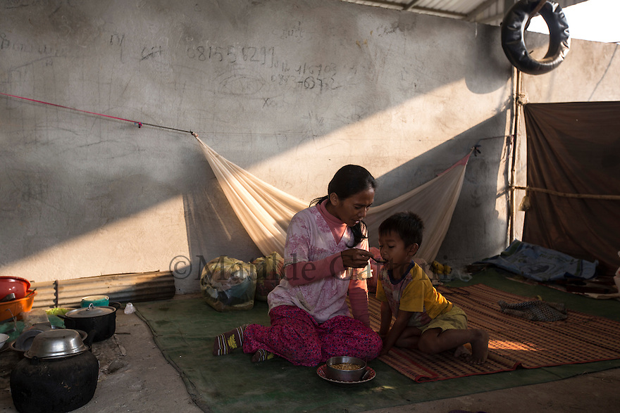 Cambodia - Kampong Speu Province - A mother is feeding her son in the camp where sugar plantation workers live nearby the Phnom Penh Sugar Company factory, in the Amliang commune. Most of them come from villages far away in the province to work in the sugar plantation during the dry season. Without a proper home they sleep in makeshift tents and beds in a concrete structure provided by the company. Some of them are able to save as little as 5 USD per month.