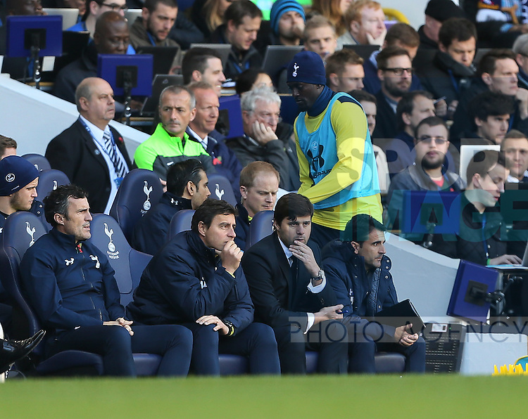 Tottenham's Emmanuel Adebayor warms up as a substitute behind manager Mauricio Pochettino<br /> <br /> - Barclays Premier League - Tottenham Hotspur vs Stoke City- White Hart Lane - London - England - 9th November 2014  - Picture David Klein/Sportimage