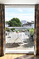 A table set for a meal on the sunny roof terrace of a Kensington flat