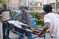 Nepalese people carry a dead body on a stretcher inside a hospital after the second earthquake hit Nepal, Kathmandu. May 12, 2015