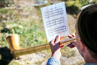 Looking at the music sheet on an alp horn. Switzerland.