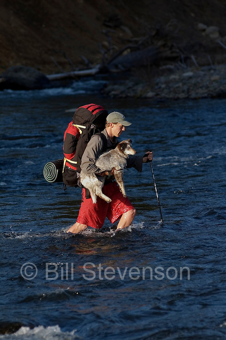 A photo of a man carrying his dog across a river near Truckee, CA.