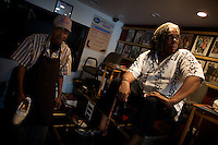 """a shoe repair and shine shop owner ( on left ) who takes in former gang members assisted by the  American Non Profit """"Cease Fire"""" and one of the NGO volunteers in Roseland, Chicago, Illinois, United States on Wednesday August 6 2008..Senator Barack Obama, the 2008 democratic party presidential candidate, begun his political career by being an organizer in these neighborhoods..Roseland and other South Side neighborhoods of Chicago are among the most violent and segregated in the country."""