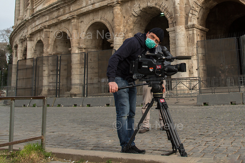 """TV Crew (in the photo, RAI TG2) & members of the Press: allowed<br /> <br /> Colosseum: Closed.<br /> <br /> Rome, 12/03/2020. Documenting Rome under the Italian Government lockdown for the Outbreak of the Coronavirus (SARS-CoV-2 - COVID-19) in Italy. On the evening of the 11 March 2020, the Italian Prime Minister, Giuseppe Conte, signed the March 11th Decree Law """"Step 4 Consolidation of 1 single Protection Zone for the entire national territory"""" (1.). The further urgent measures were taken """"in order to counter and contain the spread of the COVID-19 virus"""" on the same day when the WHO (World Health Organization, OMS in Italian) declared the coronavirus COVID-19 as a pandemic (2.).<br /> ISTAT (Italian Institute of Statistics) estimates that in Italy there are 50,724 homeless people. In Rome, around 20,000 people in fragile condition have asked for support. Moreover, there are 40,000 people who live in a state of housing emergency in Rome's municipality.<br /> March 11th Decree Law (1.): «[…] Retail commercial activities are suspended, with the exception of the food and basic necessities activities […] Newsagents, tobacconists, pharmacies and parapharmacies remain open. In any case, the interpersonal safety distance of one meter must be guaranteed. The activities of catering services (including bars, pubs, restaurants, ice cream shops, patisseries) are suspended […] Banking, financial and insurance services as well as the agricultural, livestock and agri-food processing sector, including the supply chains that supply goods and services, are guaranteed, […] The President of the Region can arrange the programming of the service provided by local public transport companies […]».<br /> Updates: on the 12.03.20 (6:00PM) in Italy there 14.955 positive cases; 1,439 patients have recovered; 1,266 died.<br /> <br /> Footnotes & Links:<br /> Info about COVID-19 in Italy: http://bit.do/fzRVu (ITA) - http://bit.do/fzRV5 (ENG)<br /> 1. March 11th Decree Law http://bit.do/fzREX (I"""