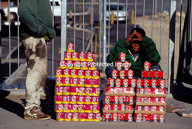 dibuven00097 .Small Business. Vendor. Boys selling canned food (tinned fish) in a market on July 19, 2001 in Site B Khayelitsha, a township about 35 kilometers outside Cape Town, South Africa. Khayelitsha is one of the poorest and fastest growing townships in South Africa. People usually come from the rural areas in Eastern Cape province to find work as maids and laborers. Most people don't find work and the unemployment rate is very high, together with lot of violence and a growing HIV-Aids epidemic itÕs a harsh area to live in..©Per-Anders Pettersson/iAfrika Photos.