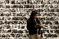 A professional business workers checks her blackberry in front of a water fountain in uptown Charlotte, NC.