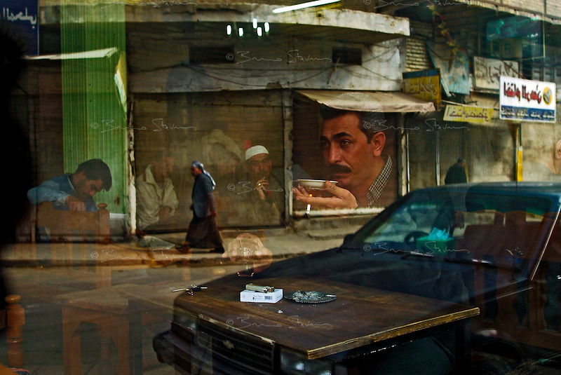 Baghdad, Iraq, February 12, 2003.The window of the Al Zahawi cafe in Rashid street, named after a famous local poet and musician...Baghdad cafes are a trademark of this ancient city, men gather after prayer and play dominoes or blackjack with intense passion while drinking black or lemon tea or traditionnal arabic coffie (ka'wah). .As the American menace of invasion draws nearer, tension is clearly perceptible: in any war, the civilian population endures a heavy burden...
