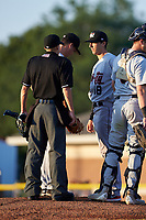 Tri-City ValleyCats pitching coach Bill Murphy (18) talks with pitcher Nathan Thompson (17) as umpire Matt Baldwin listens in during a game against the Batavia Muckdogs on July 15, 2017 at Dwyer Stadium in Batavia, New York.  Tri-City defeated Batavia 5-4.  (Mike Janes/Four Seam Images)