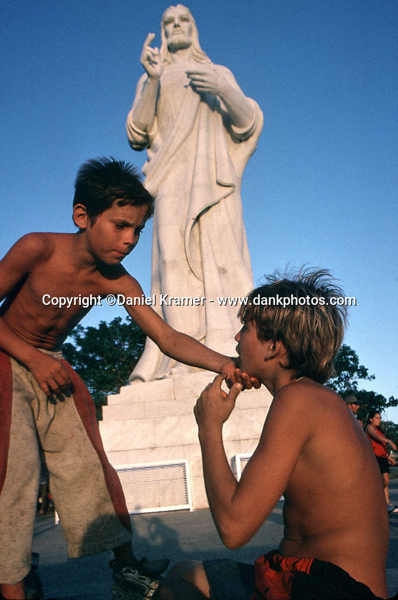 Young boys play around the Christ of Havana sculpture overlooking the bay in Havana, Cuba.