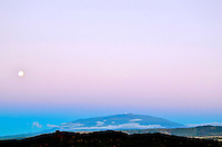 At dusk, the full moon rises over majestic Mauna Kea, as viewed from Ka'upulehu, North Kona, island of Hawai'i.