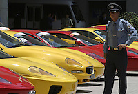 A Chinese security guard stands by parked Ferrari and Maserati sports cars in Shanghai, China. The Ferrari Maserati group opened a new showroom today in China's wealthiest city, marking the Italian luxury car maker's optimistic look of the Chinese market..