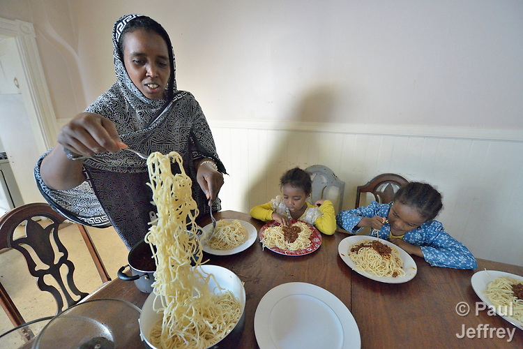 Lula Abubakar, a recently arrived refugee from Eritrea, serves spaghetti to her family, including daughters Saliha, 5, and Nasrin, 6, in Lancaster, Pennsylvania. The family was resettled in the United States by Church World Service. <br /> <br /> Photo by Paul Jeffrey for Church World Service.