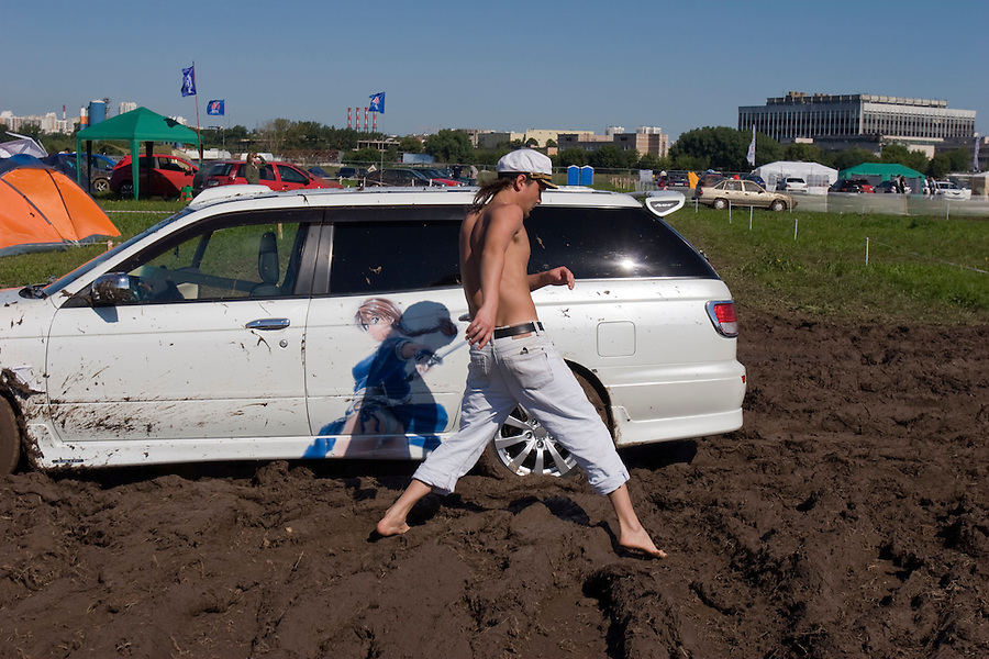 Moscow, Russia 12/07/2008..A visitor makes his way past a car stuck in the mud at the annual Autoexotica Show, a ten day festival that attracts thousands of Russian motor enthusiasts. Figures show the Russian auto market has just overtaken Germany's to become the largest in Europe, and analysts predict that within four years it will be the third largest in the world.