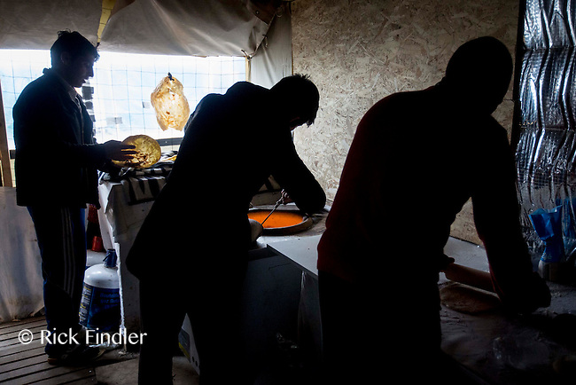 FRANCE, Calais: 18 December 2015 Refugees form an assembly line as they make and prepare to sell fresh bread in the refugee camp known as 'The Jungle'. The camp in Calais is now believed to hold 7,000 refugees, who are all trying to prepare for the cold winter months ahead.<br /> Rick Findler / Story Picture Agency