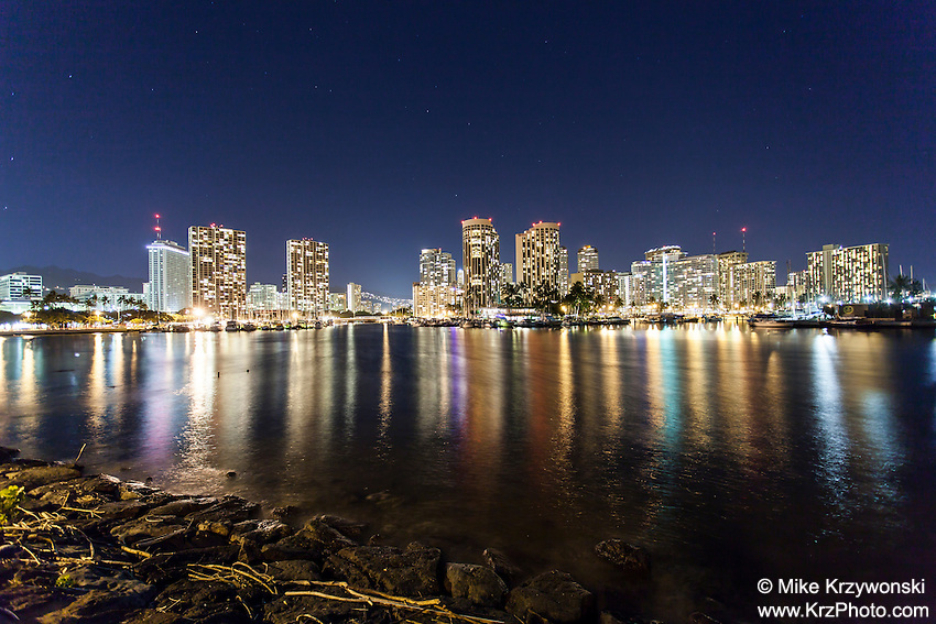 View of Waikiki buildings at night with lights reflecting on water, Magic Island, Honolulu