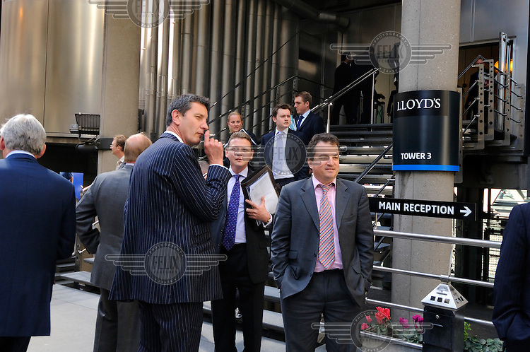 Smoking businessmen outside Lloyds of London in the City.
