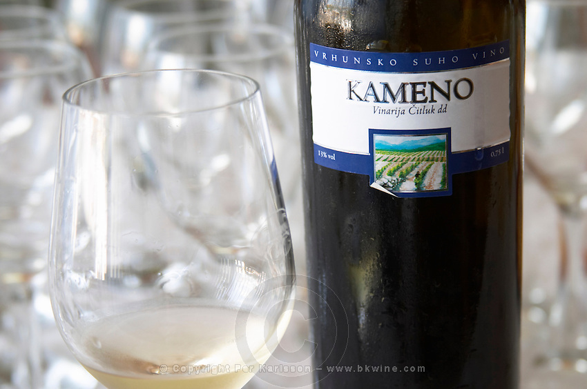 Wine glasses in the tasting room. Bottle of Kameno Vrhunsko Suho Vino white wine from their best vineyard. Detail of label with a picture of the vineyard. Vinarija Citluk winery in Citluk near Mostar, part of Hercegovina Vino, Mostar. Federation Bosne i Hercegovine. Bosnia Herzegovina, Europe.