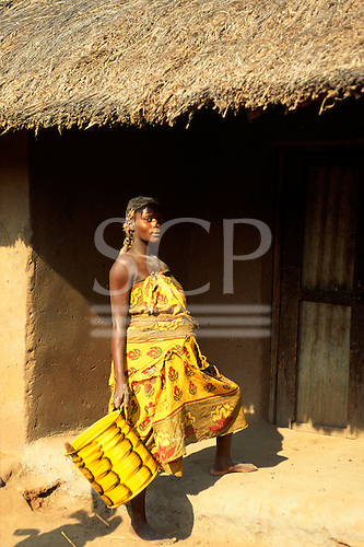 Yumba, Tanzania. Woman wearing ragged printed cotton clothes carrying a yellow can outside an adobe and thatch hut.