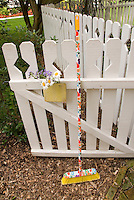 Open garden gate in fence with welcoming flowers and painted broom