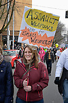 "Carrying a sign linking assault weapons with inadequate penis size, this woman was among hundreds of Seattle residents who marched from Westlake Center Park to the Seattle Center on January 13, 2013, calling for stricter regulations of firearms. Sponsored by a network of churches and other groups called ""Stand-up Washington,"" the demonstrators called for a state ban on semi-automatic weapons as well as stricter gun laws."