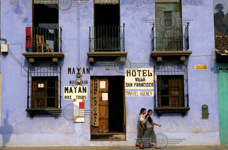 Young women walking past a hotel building (which also advertises travel agency, telephone and tourism services) in the colonial town of Antigua.