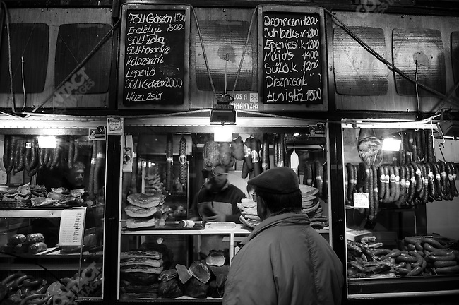 A customer queued up at a meat and sausage stall at a market on Csengery Street in Budapest, Hungary, March 23, 2008