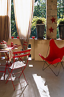 A red Butterfly chair and metal garden table and chairs are arranged on this sunlit terrace