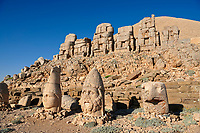Statue heads, from right,  Lion, Eagle, Herekles & Apollo,  with headless seated statues in front of the stone pyramid 62 BC Royal Tomb of King Antiochus I Theos of Commagene, east Terrace, Mount Nemrut or Nemrud Dagi summit, near Adıyaman, Turkey
