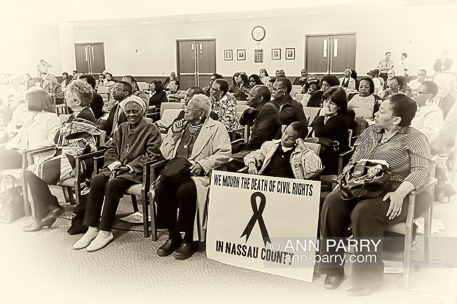 """May 9, 2011 - MINEOLA, NY:  Amid adults at public hearing, young Ramel Smith, Jr., sitting with sign: """"We Mourn the Death of Civil Rights in Nassau County."""" Front row, 4th from right, Golena White of Hempstead. Nassau County Legislature's public hearing on Legislative Redistricting, at Nassau County Executive and Legislative Building, 1550 Franklin Avenue, Mineola, Long Island, New York, USA."""
